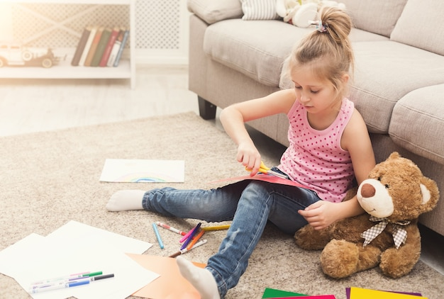 Glückliches kleines mädchen, das zu hause mit kreativem hobby beschäftigt ist. nettes kind, das mit schere und farbigem papier auf dem boden sitzt. diy, kreatives kunsthobby, frühes entwicklungs- und inspirationskonzept