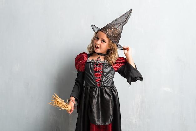 Glückliches kleines mädchen gekleidet als hexe für halloween-feiertage