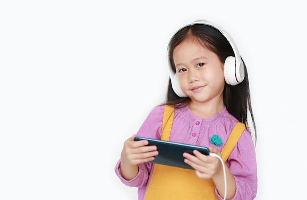 Glückliches kleines mädchen genießt hörende musik mit kopfhörern durch den smartphone, der über weiß lokalisiert wird.