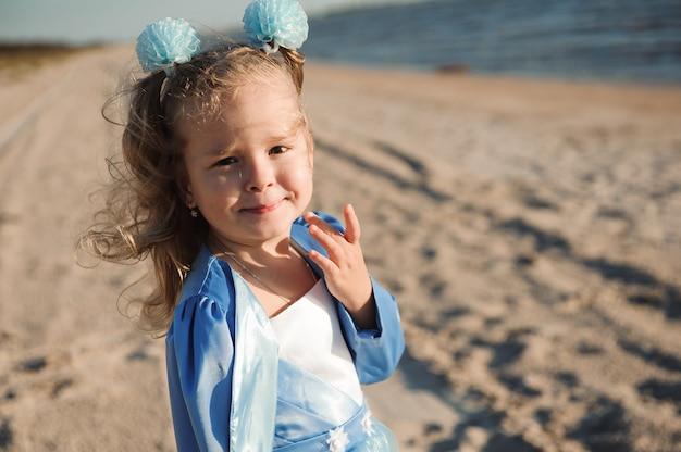 Glückliches kleines mädchen im blauen kleid am strand