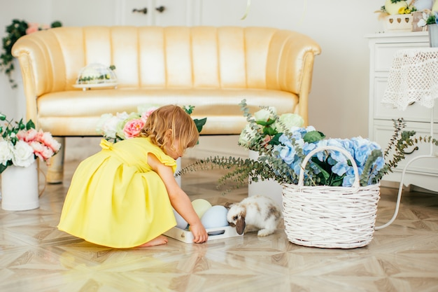 Glückliches kleines mädchen im gelben kleid mit kaninchen, blumen und eiern. grußkarte, ostern