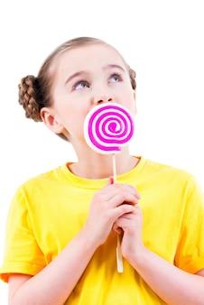 Glückliches kleines mädchen im gelben t-shirt, das farbige süßigkeiten isst - lokalisiert auf weiß.