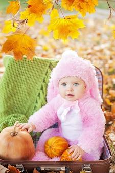 Glückliches kleines mädchen im halloween-kostüm, das kürbis hält.