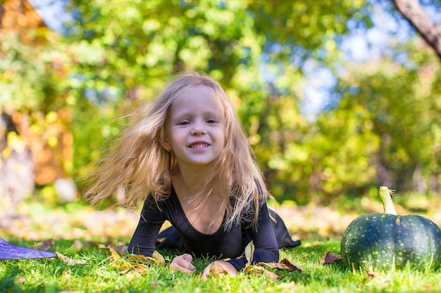 Glückliches kleines mädchen im halloween-kostüm mit steckfassungskürbis. süßes sonst gibt's saures