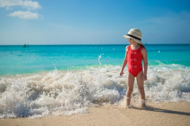 Glückliches kleines mädchen im hut am strand während der karibischen ferien