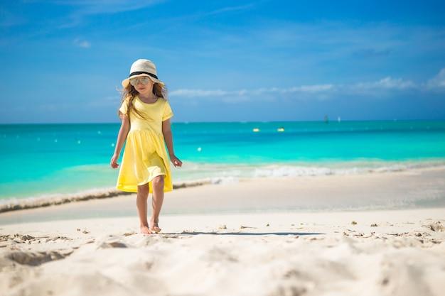 Glückliches kleines mädchen im hut auf strand während der sommerferien