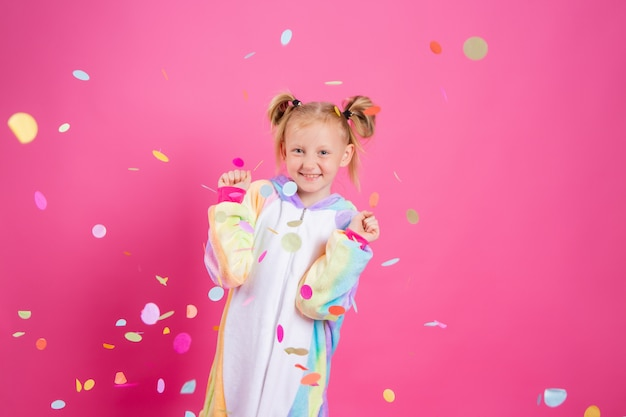 Glückliches kleines mädchen im kigurumi-einhorn auf einer rosa wand freut sich über mehrfarbiges konfetti