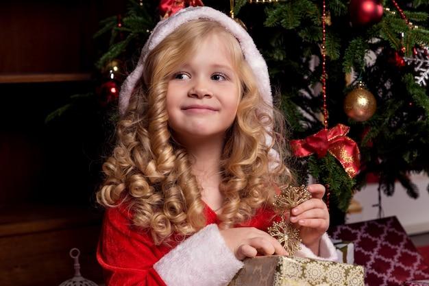 Glückliches kleines mädchen im kleid mit haben ein weihnachtsgeschenk