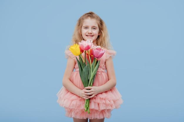 Glückliches kleines mädchen im rosa kleid mit frühlingsblumen in der hand, lokalisiert auf blauer wand