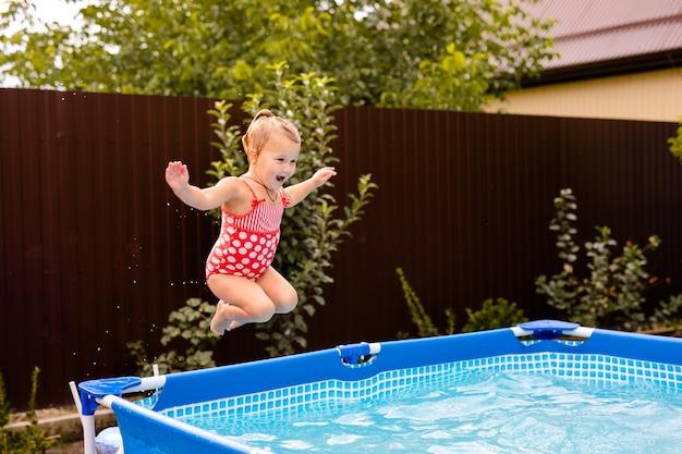 Glückliches kleines mädchen im roten badeanzug, das zu hause ins freibad springt. babymädchen, das schwimmen lernt. wasserspaß für kinder.