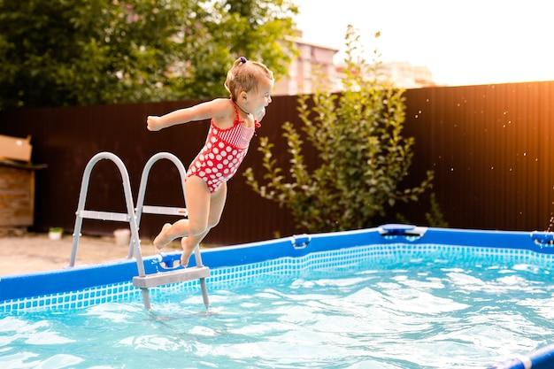 Glückliches kleines mädchen im roten badeanzug, der in den außenpool zu hause springt. baby lernen schwimmen. wasserspaß für kinder.
