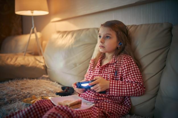Glückliches kleines mädchen im schlafanzug, der auf sofa sitzt, das pizza isst