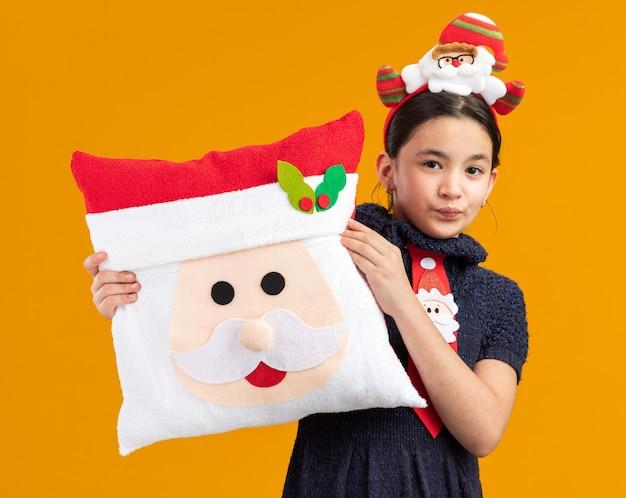 Glückliches kleines mädchen im strickkleid, das rote krawatte mit lustigem rand auf kopf hält, der weihnachtskissen hält, das mit lächeln auf gesicht schaut