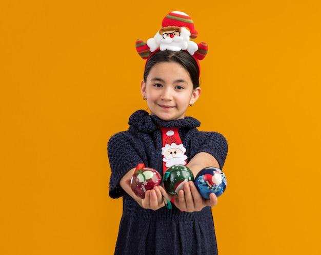 Glückliches kleines mädchen im strickkleid, das rote krawatte mit lustigem rand auf kopf hält, der weihnachtskugeln hält, die glücklich und positiv mit lächeln auf gesicht schauen