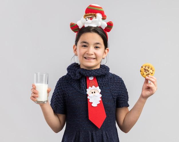Glückliches kleines mädchen im strickkleid, das rote krawatte mit lustigem weihnachtsrand auf kopf hält, der glas milch und keks hält, der fröhlich lächelt