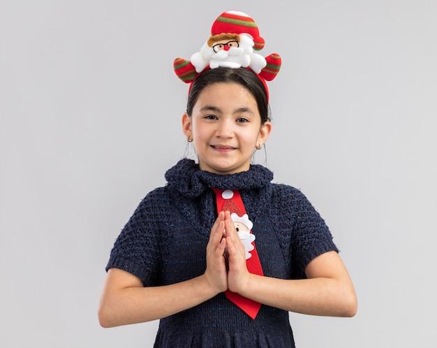 Glückliches kleines mädchen im strickkleid, das rote krawatte mit lustigem weihnachtsrand auf kopf hält, der hände zusammenhält wie namaste geste