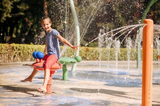 Glückliches kleines mädchen in den spritzern auf wasserspielplatz im sommerpark. kinderfreuden im aquapark