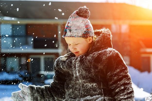 Glückliches kleines mädchen in den weißen handschuhen gehend in den winterpark wirft schnee oben