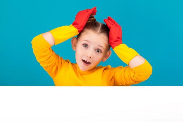 Glückliches kleines mädchen in der gelben strickjacke auf blauem hintergrund