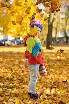 Glückliches kleines mädchen in der hellen kleidung, die mit blättern in einem stadtpark im herbst spielt