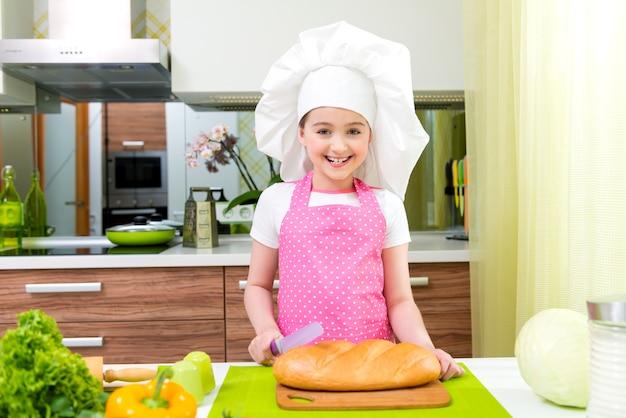 Glückliches kleines mädchen in der rosa schürze, die brot in der küche schneidet.
