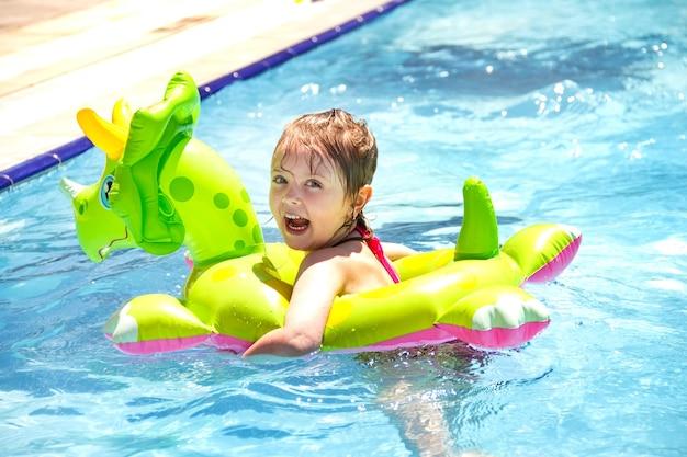 Glückliches kleines mädchen in einem aufblasbaren kreis, das im sommer im pool lacht