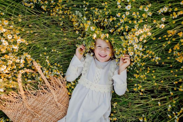 Glückliches kleines mädchen in einem baumwollkleid liegt im sommer bei sonnenuntergang auf einem feld von gänseblümchen. lacht, ansicht von oben