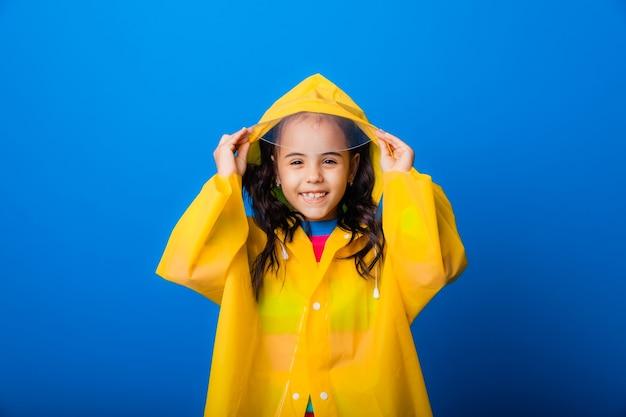 Glückliches kleines mädchen in einem gelben regenmantel und roten stiefeln auf blauem hintergrund.