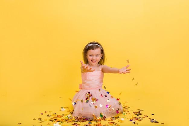 Glückliches kleines mädchen in einem geschwollenen rosa kleid fängt konfetti mit ihren händen auf einem gelben lokalisierten