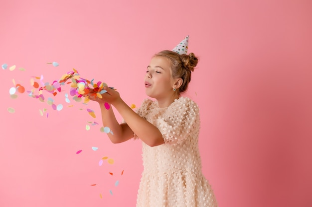 Glückliches kleines mädchen in einer geburtstagskappe bläst ihre handflächen mehrfarbiges konfetti auf einem rosa hintergrund im studio ab