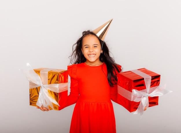 Glückliches kleines mädchen in einer geburtstagsmütze hält eine große rote geschenkbox. urlaubskonzept, platz für text