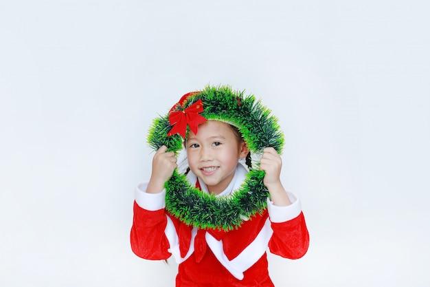 Glückliches kleines mädchen in sankt-kostüm, das weihnachtsrunden kranz auf ihrem gesicht auf weißem bac hält