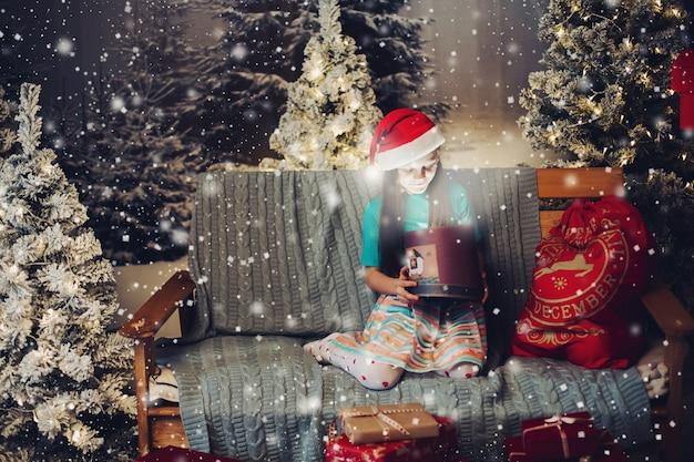 Glückliches kleines mädchen in santa claus-hut mit geschenk auf couch.