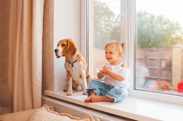 Glückliches kleines mädchen in weißer bluse und jeans und ihr beagle-hund sitzen am fenster
