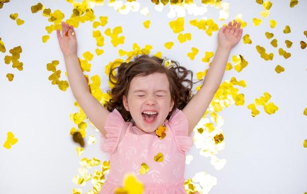 Glückliches kleines mädchen liegt mit goldenem konfetti auf weißem hintergrund mit einem platz für text. glückliche kindheit