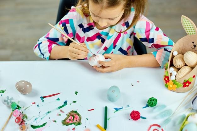 Glückliches kleines mädchen malt, zeichnung mit bürsteneiern zu hause. kind bereitet sich auf ostern vor, hat spaß und feiert fest. frohe ostern, diy