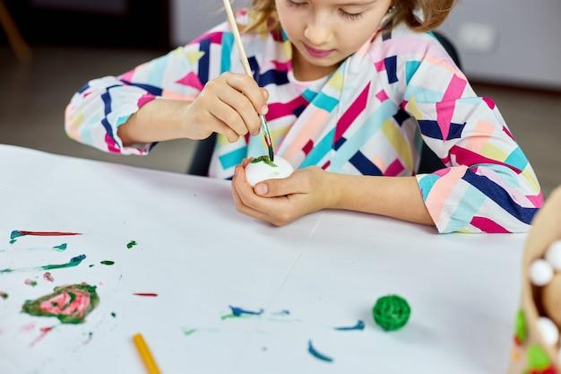 Glückliches kleines mädchen malt, zeichnung mit bürsteneiern zu hause