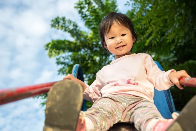 Glückliches kleines mädchen mit dem herbstspielen im freien im frühjahr parken
