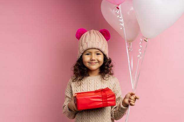 Glückliches kleines mädchen mit dem lockigen haar, das warmen pullover, wintermütze mit flauschigen pompons trägt, rote geschenkbox und luftballons hält, lokalisiert lächelnd