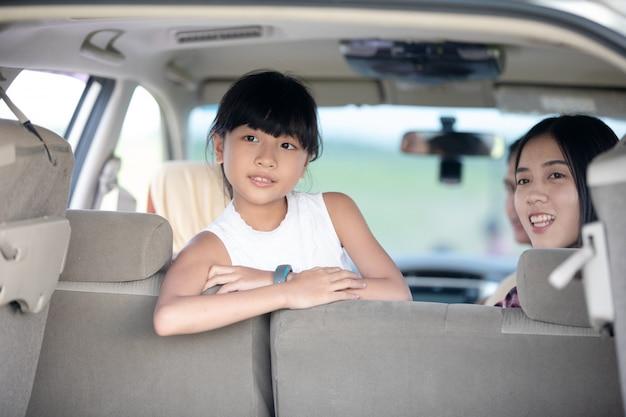 Glückliches kleines mädchen mit der asiatischen familie, die im auto sitzt