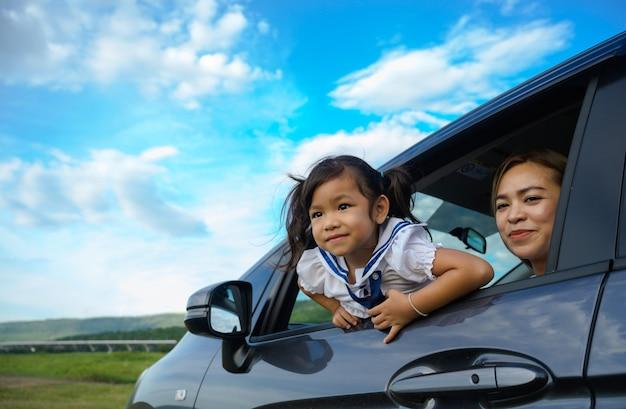 Glückliches kleines mädchen mit der familie, die im auto sitzt.