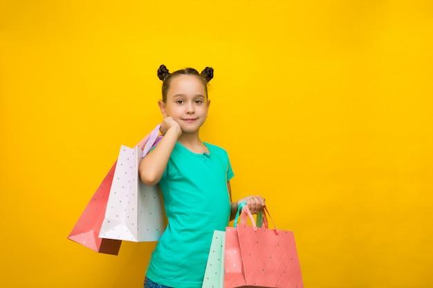 Glückliches kleines mädchen mit der lustigen endstückstellung lokalisiert über dem gelben hintergrund, der einkaufstaschen hält.