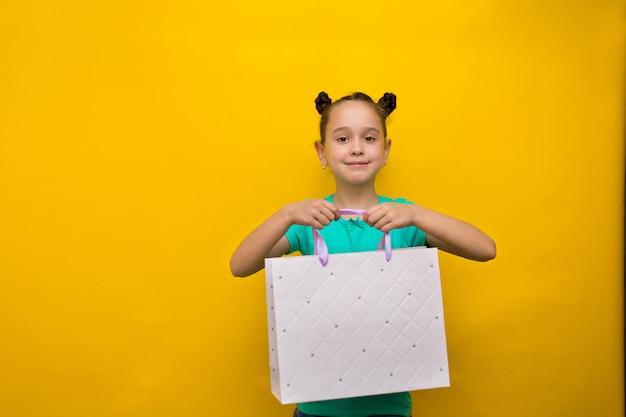 Glückliches kleines mädchen mit der lustigen endstückstellung lokalisiert über der gelben wand, die einkaufstaschen hält. kamera suchen