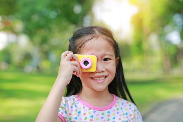 Glückliches kleines mädchen mit digitalkameraspielzeug im garten im freien.