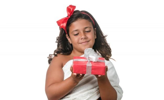 Glückliches kleines mädchen mit einem geschenk auf weißem hintergrund