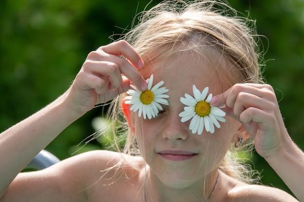 Glückliches kleines mädchen mit gänseblümchen auf den augen. sommer