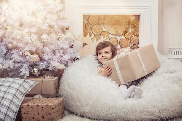 Glückliches kleines mädchen mit geschenken in schönen kästen im weihnachtsinnenraum