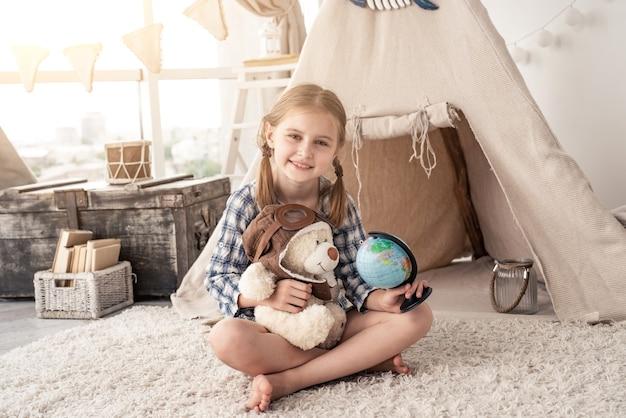 Glückliches kleines mädchen mit globus und teddybär, das auf dem boden vor wigwam sitzt