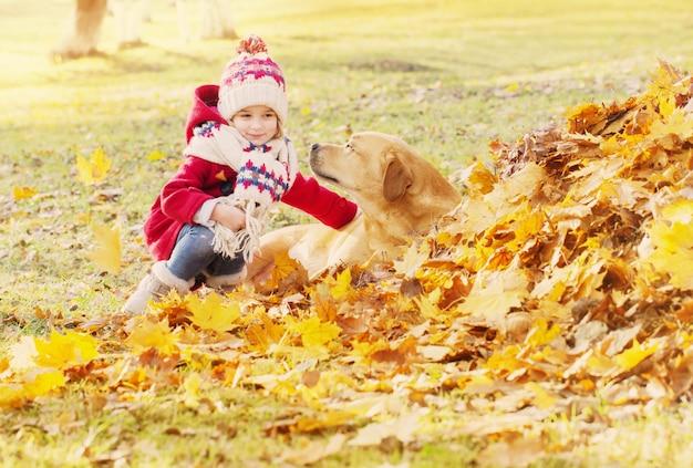 Glückliches kleines mädchen mit hund im herbstpark