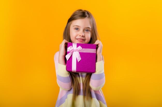 Glückliches kleines mädchen mit langen haaren, die eine rosa geschenkbox auf einem gelben raumisolat halten